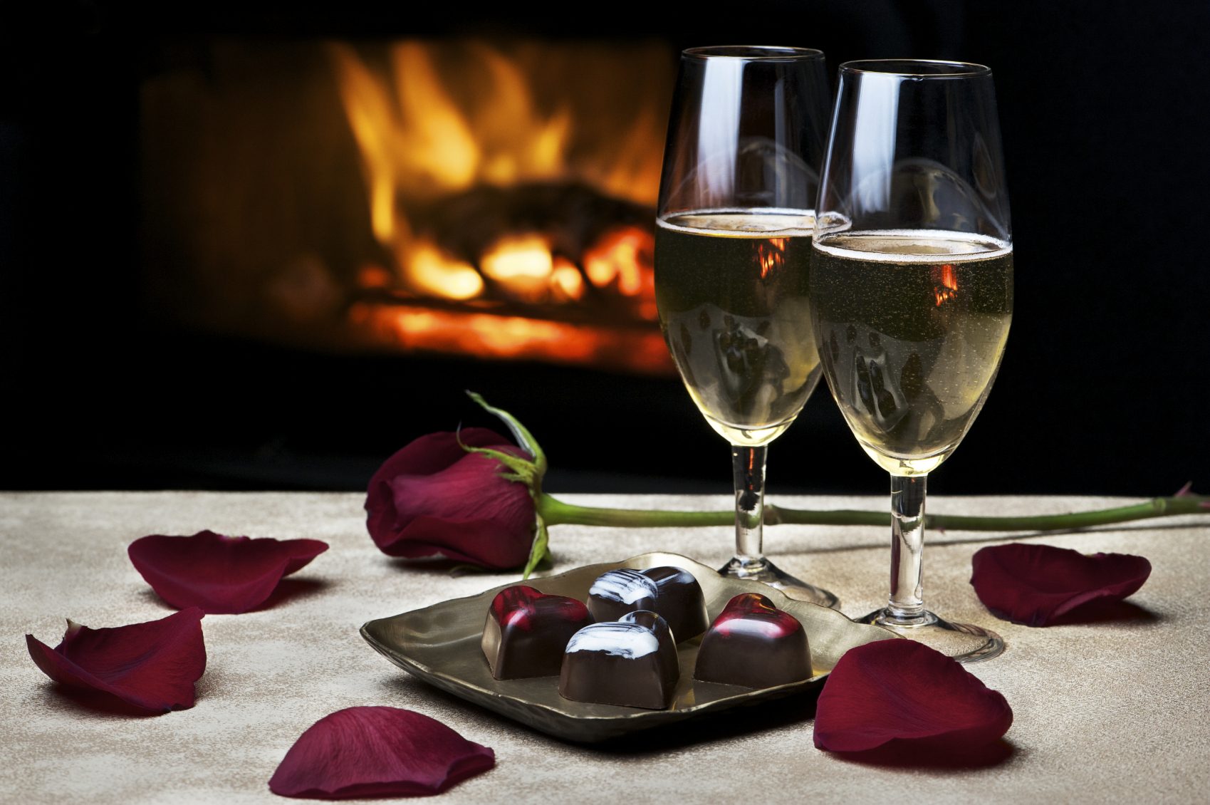 On a white table sits rose petals, 2 glasses of champagne, and a tray with four decadent chocolates.  In the background a fireplace burns in the fireplace.