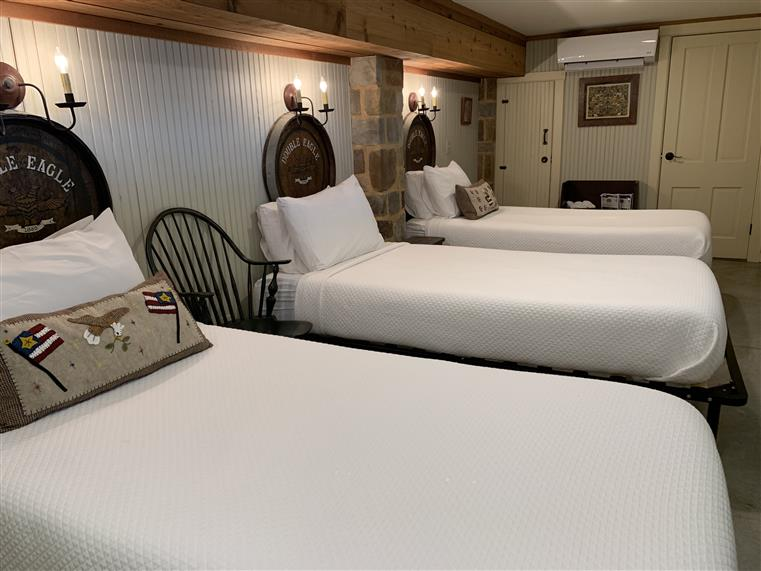 The Double Eagle Cellar is a guestroom that has three twin beds in it.  There are light fixtures on the wall behind each bed, and the room has a private bathroom