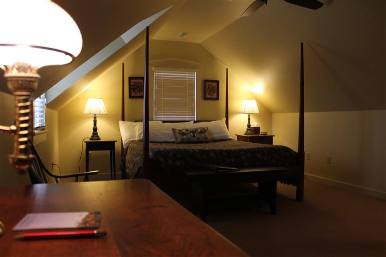 The king bed is in the background, night stands with lamps are on each side of the bed.  In the foreground is a tabletop with a pen and pad of paper, illuminated by another lamp.