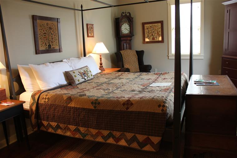 The king-sizd bed is the main focus.  In the background is a grandfather clock, and a soft chair with a shawl draped over it.  Artwork hangs over the bed, and a chest is at the foot of the bed.