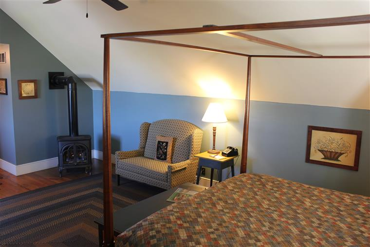 This photo, taken from the side of the King-sized bed shows a small sitting area and a gas stove fireplace.