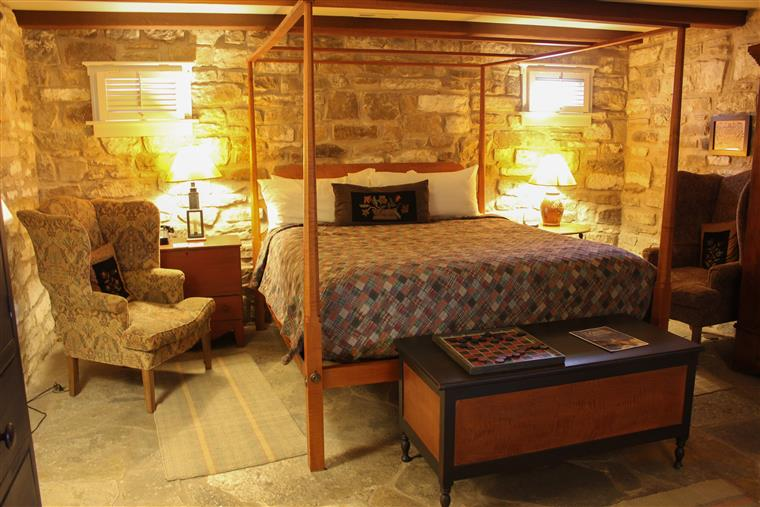 This is the King bed in the Vidal room.  This room is a cellar room and has stone walls and floors.  Soft chairs flank each side of the bed, and a chest sits at the foot of the bed with a checkers game.