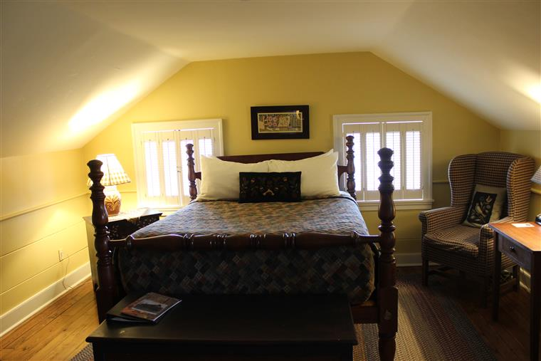 This photos shows the queen bed in the guestroom.  There is a small piece of artwork over th ehead of the bed, and windows on each side with wooden blinds.  There is a soft chair on the right of the bed with a pillow on it.  On the left of the bed is a lamp and night stand.