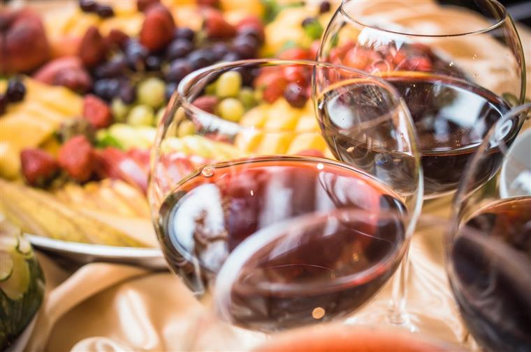 glasses of red wine with fruit in the background