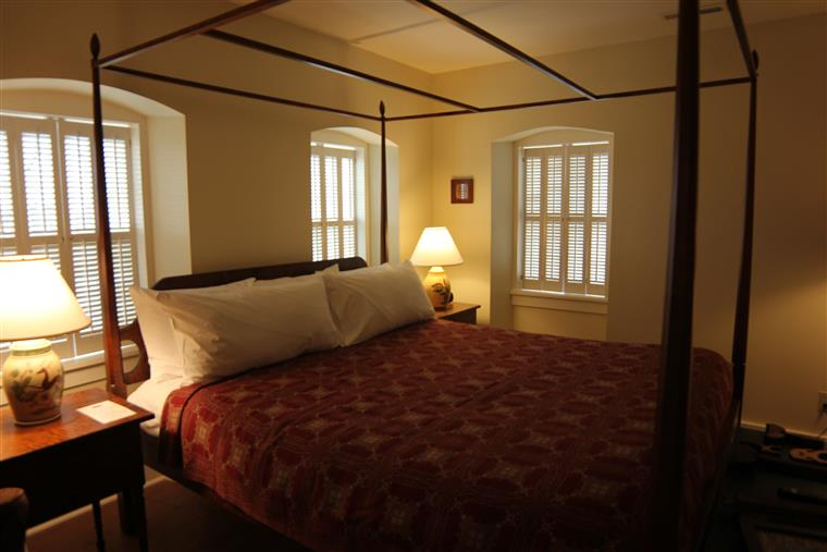 The Bedchambers has a california king bed with a pencil-post bed frame and a red quilt.  Three wwindows surround the bed and two side tables.
