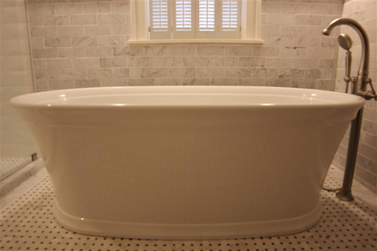A close-up of a porcelain soaking tub.  A faucet and shower head rest to the right of the tub.