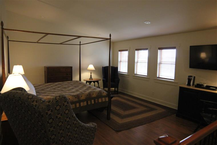 The bed chambers for the Stonewerks.  A pencil post california king bed small sitting area, and three westward-facing windows highlight this room.  TV and coffee service is in the far right of the photo.