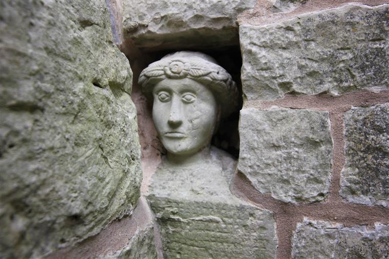 A close up of a stone figure built into a stone wall that is outside the Stonewerks.