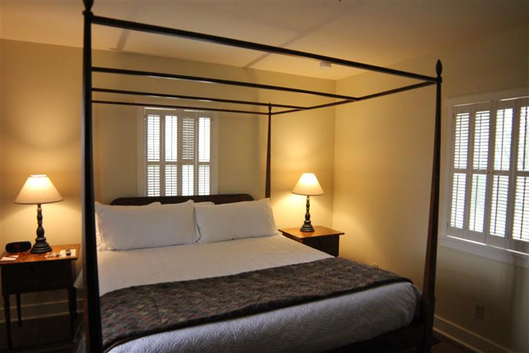 The bed chambers for the Violin shop are filled by a pencil-post california king bed, with night stands on both sides.  The room is lit by two windows and lamps on the night stands.
