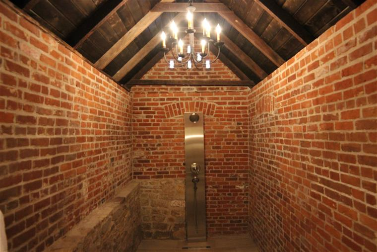 The shower for the violin shop is a brick and stone structure with a wooden catherdral ceiling.  A chandelier with about a dozen light bulbs hangs in the middle of the space.