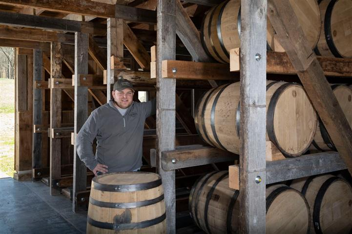 male standing behind wine barrel