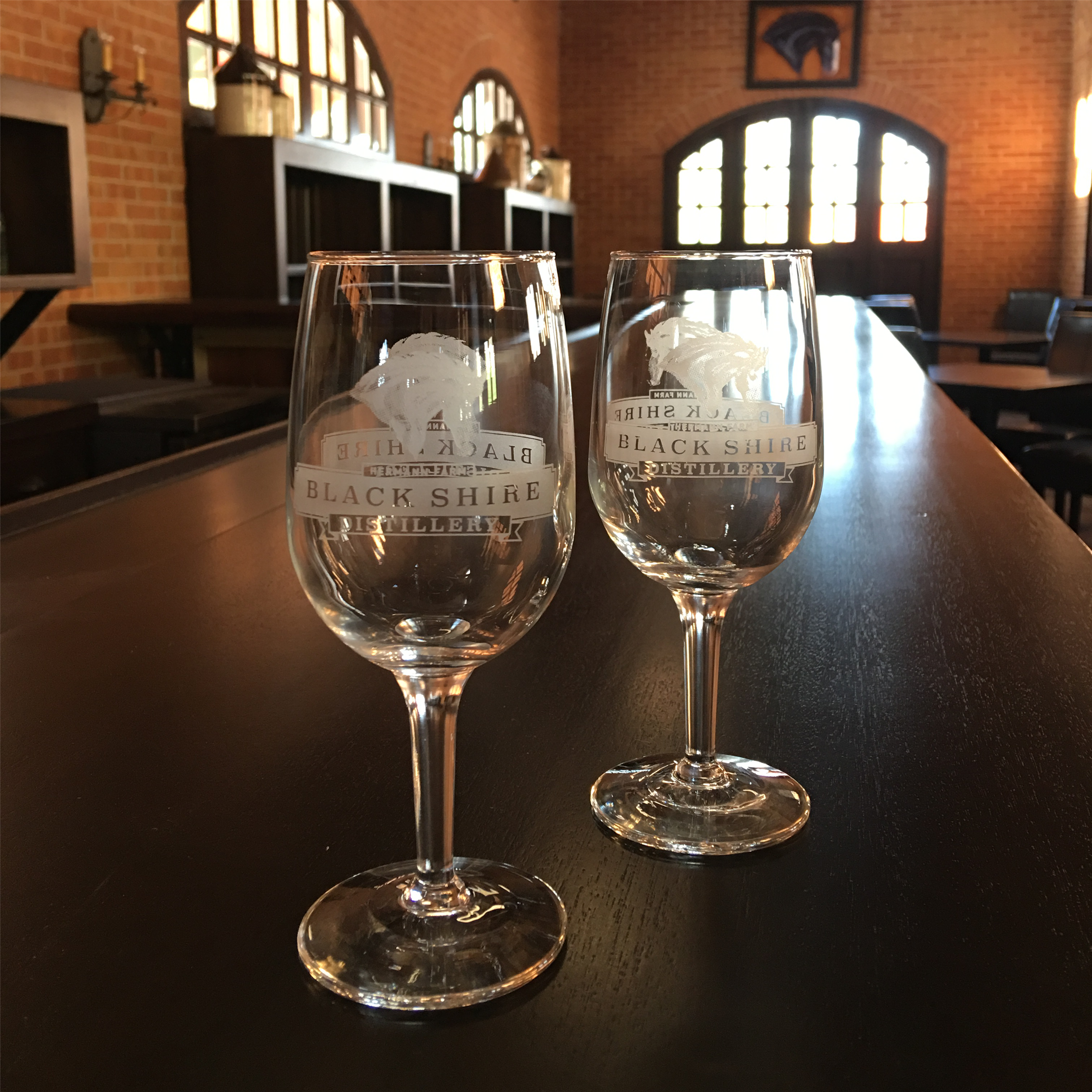 two wine glasses with black shire distillery logo