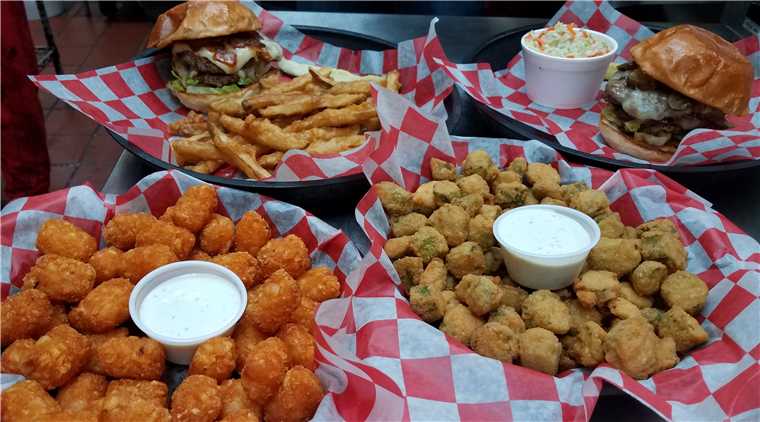 various trays of burgers and fried food