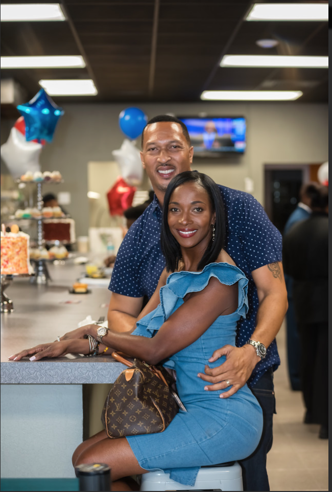 Man and woman at counter posing for photo