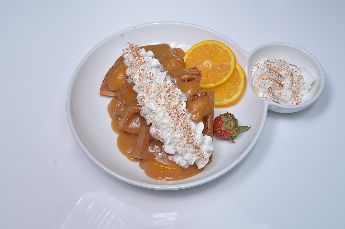 Peach cobbler waffle. House-recipe Belgium waffle topped with homemade peach cobbler and whipped cream.
