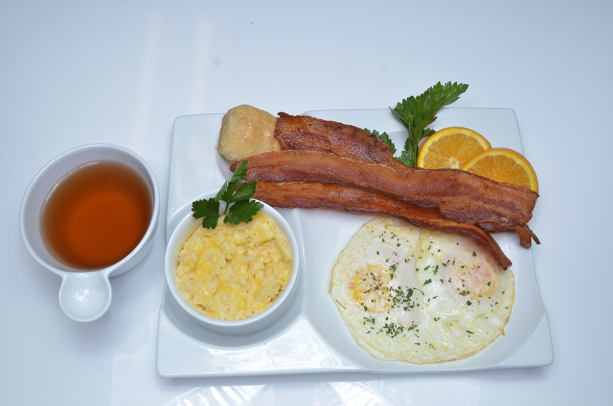 Two eggs, bacon strips, grits, biscuit, garnished with oranges.