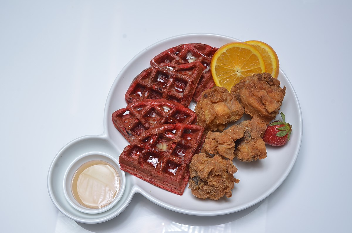 Chicken and waffles garnished with orange slices and strawberry.