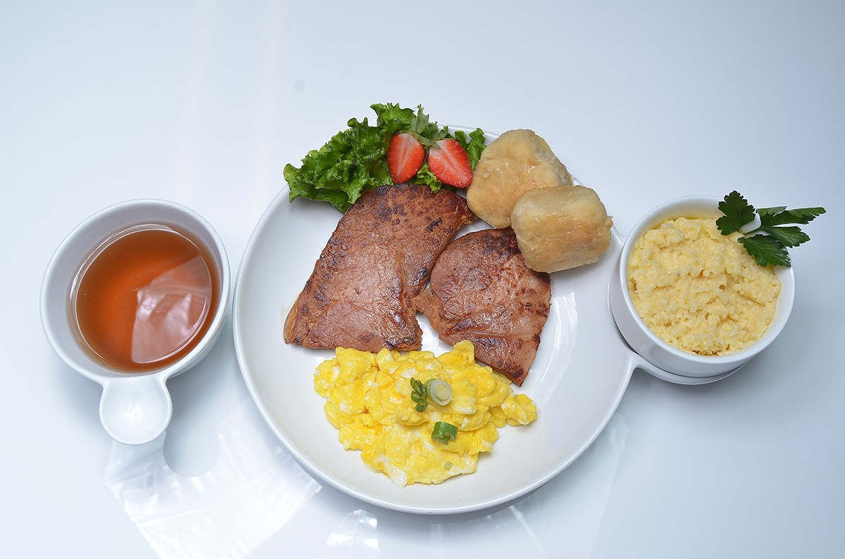 Scrambled eggs, two biscuits, strawberries, grits