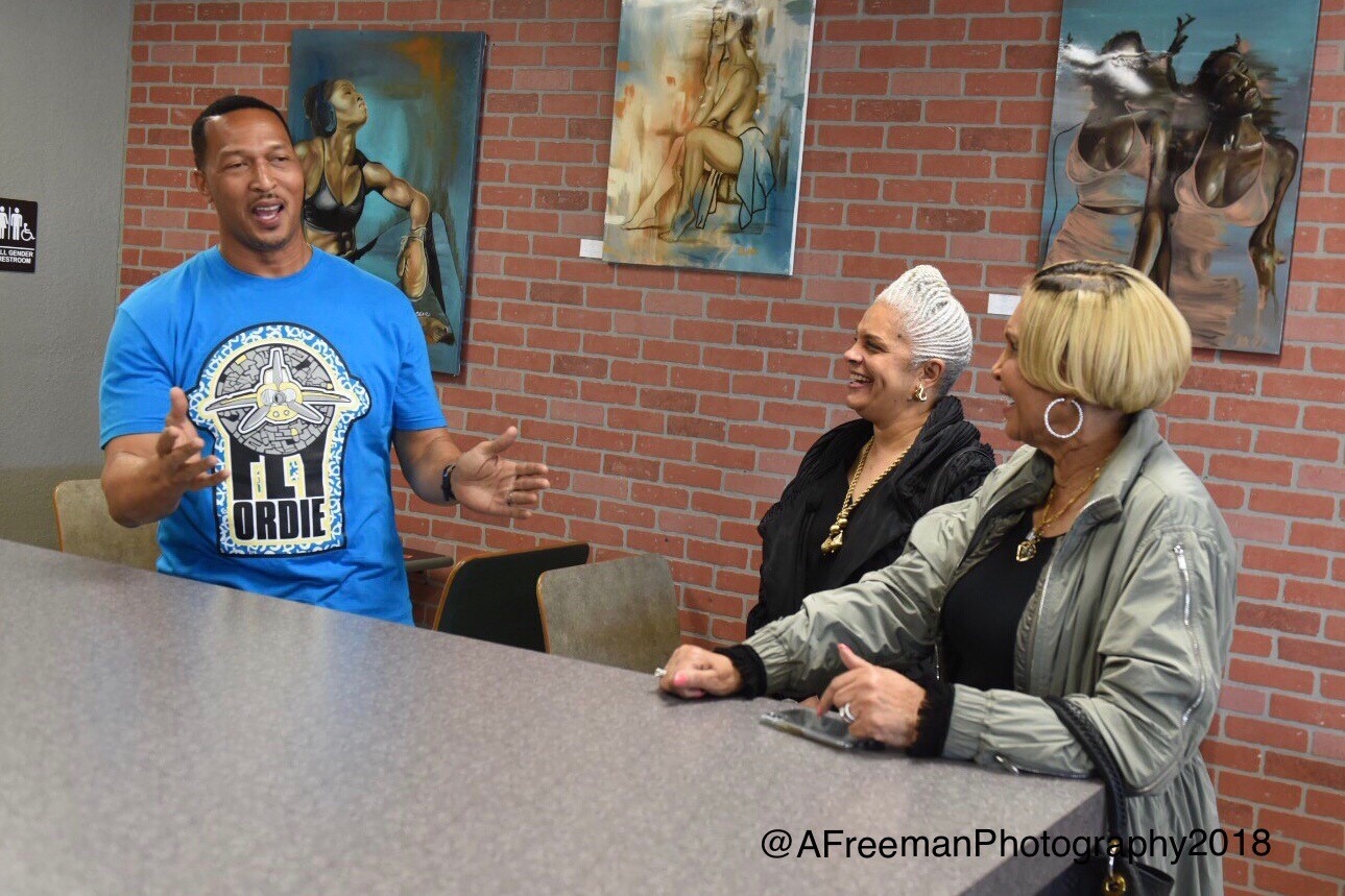 Man speaking to two women at service counter