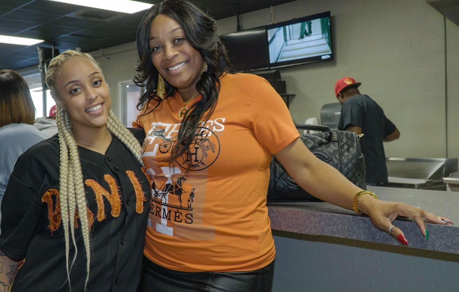 Two women posing for photo at service counter