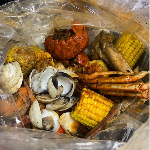 Clam, lobster, crab legs, corn in a bag.