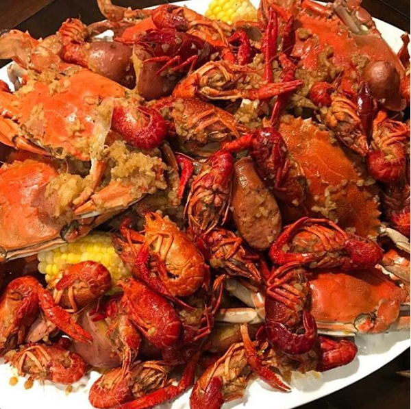 Seasoned crawfish and whole crab with corn on a plate.