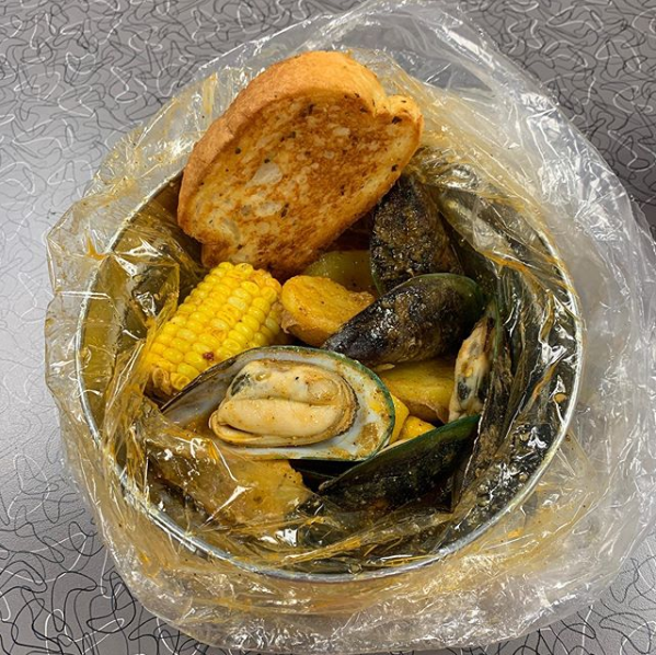 Seasoned Mussels, Corn, & Bread in a bowl.