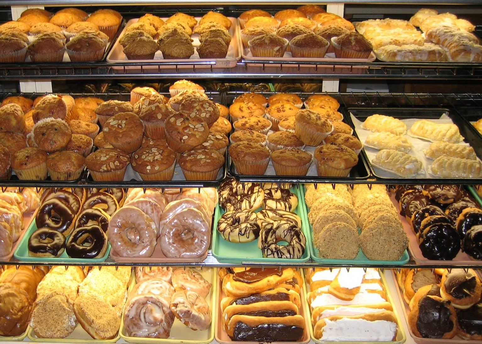 Pastry case filled with a variety of pastries including donuts, cookies, eclairs and muffins.
