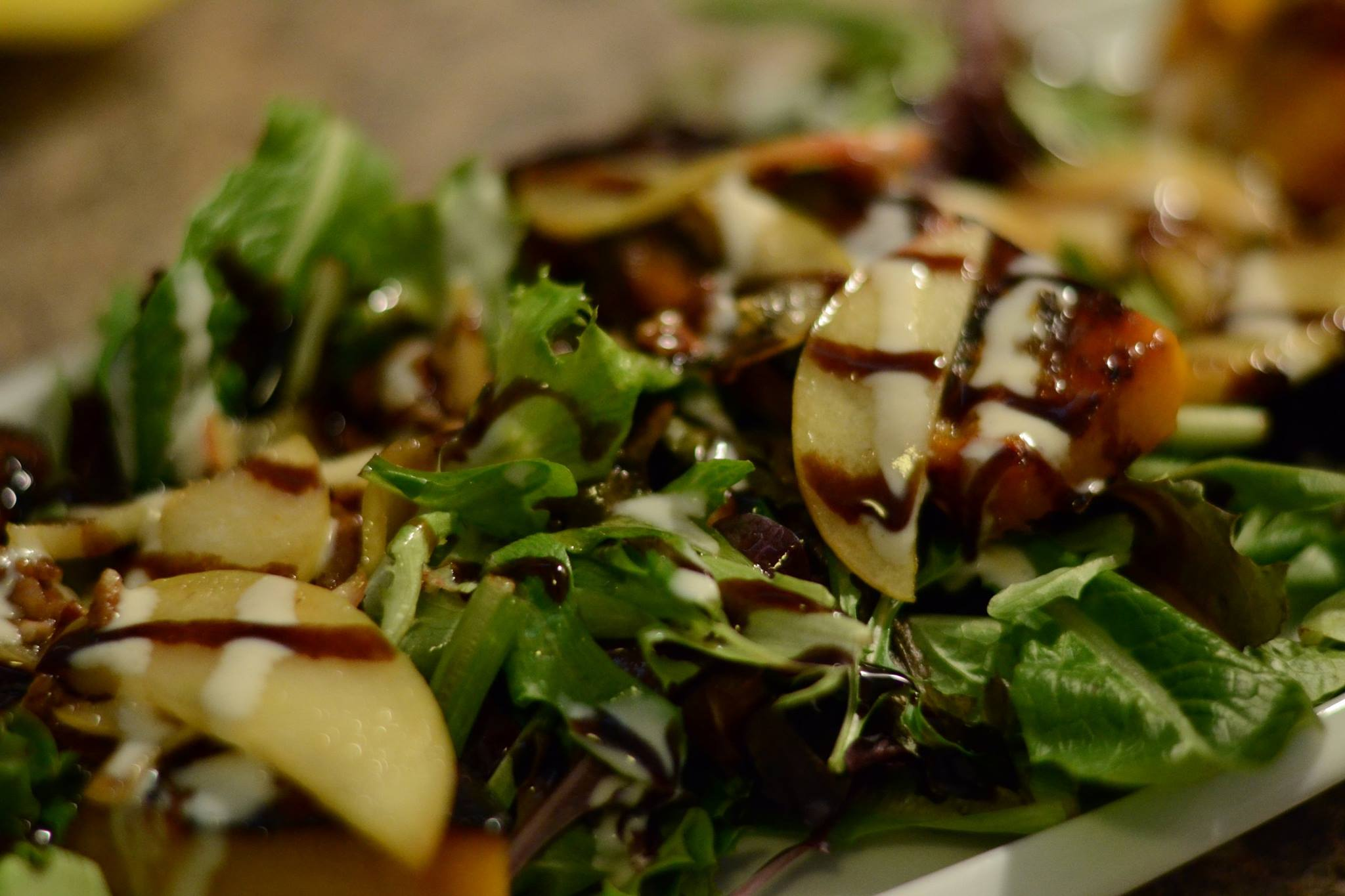 Salad with apple slices, tomatoes, balsamic drizzle