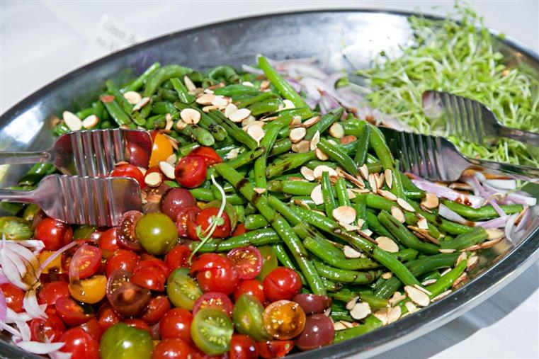 baby tomatoes, green beans topped with almonds and cole slaw in a tray