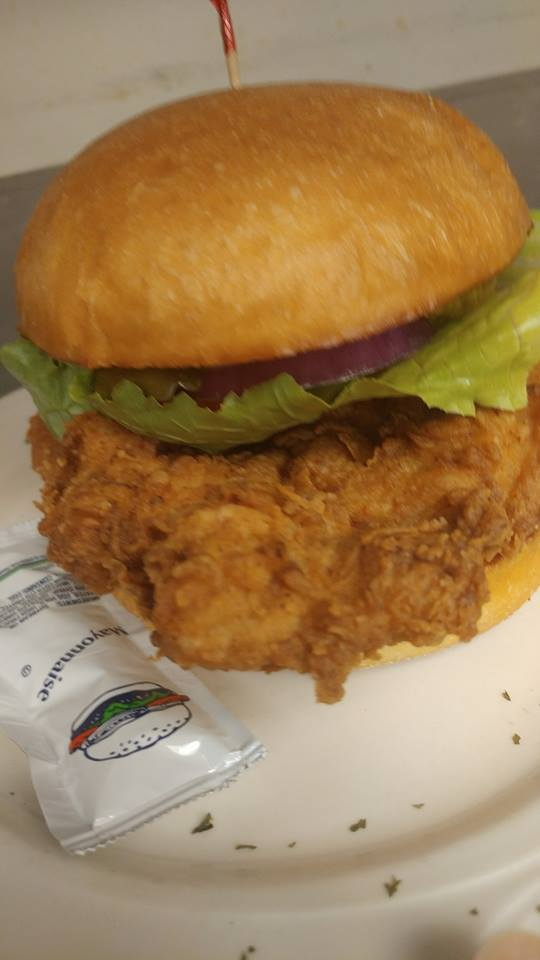 Chicken sandwich on bun with lettuce and onion.