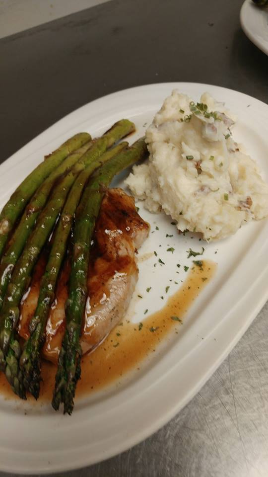Pork steak. Hearty pork steak brushed with Cannonball BBQ sauce. Topped with asparagus, side of mashed potatoes.
