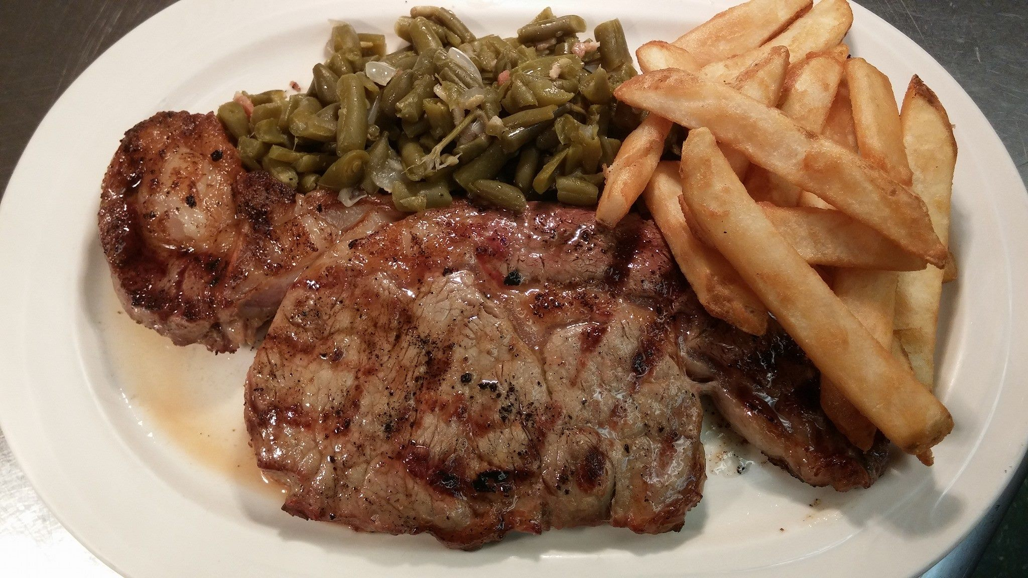 Ribeye steak. cut of beef seasoned perfectly and char-grilled to order with fries and green beans.