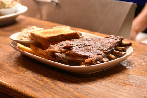 Plate of ribs with fries and toast on wood tabletop.