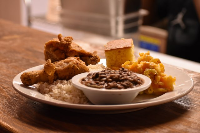 Plate of fried chicken, mac and cheese, rice, beans, cornbread