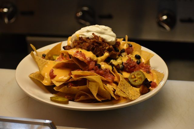 Boomers' loaded nachos with pulled pork, sour cream, beer cheese, black beans, jalapenos on white dish