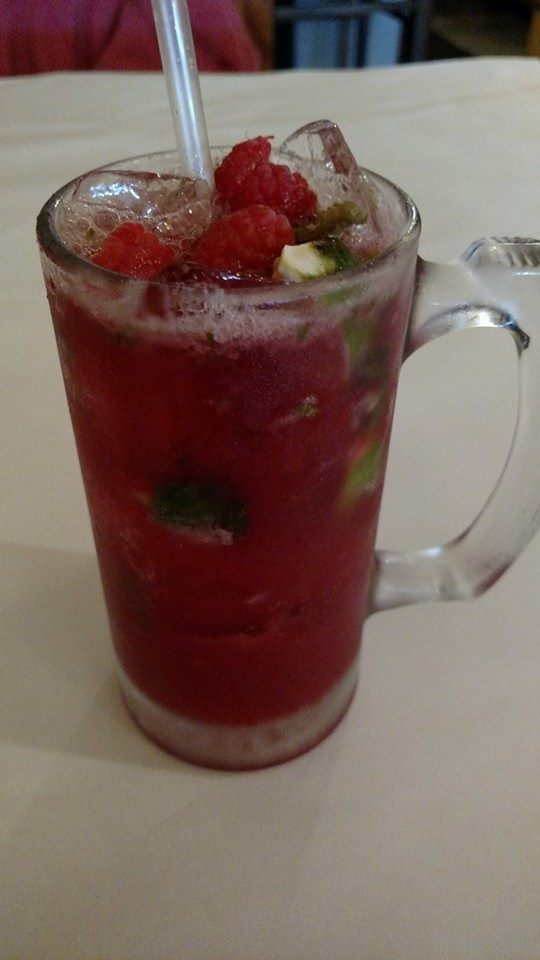 Red drink over ice with mixed fruit inside