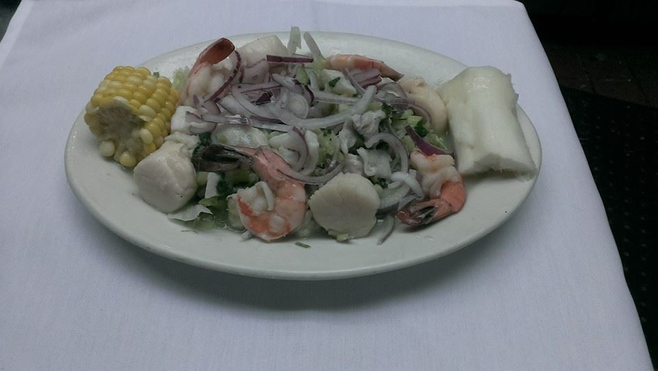 A seafood salad with scallops, shrimp, greens, strings of red onions and a small side cob of corn