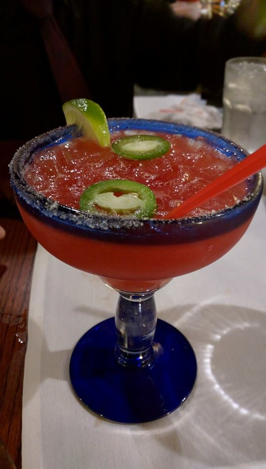 Red mixed drink in a margarita glass with a salt rim with jalapenos and a wedge of lime