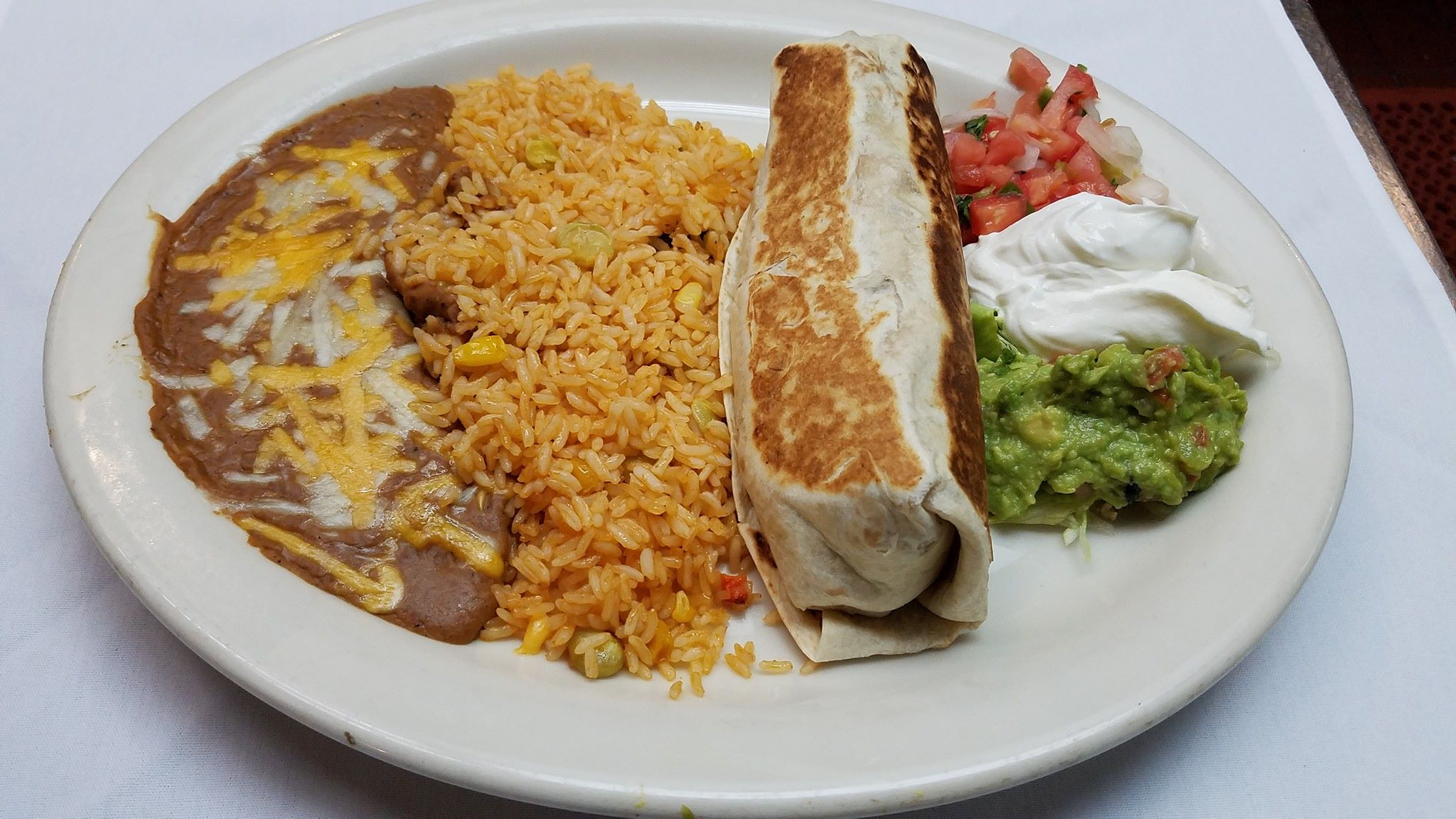 A flour filled tortilla served with yellow Mexican rice, refried pinto beans, lettuce, pico de gallo, guacamole, and sour cream