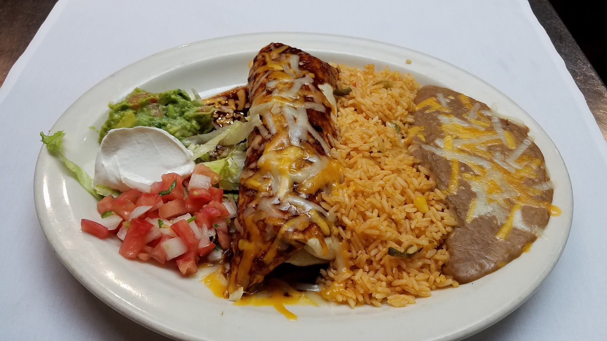 A flour filled tortilla topped with a homemade sauce and melted cheese; served with yellow Mexican rice, refried pinto beans, lettuce, pico de gallo, guacamole, and sour cream