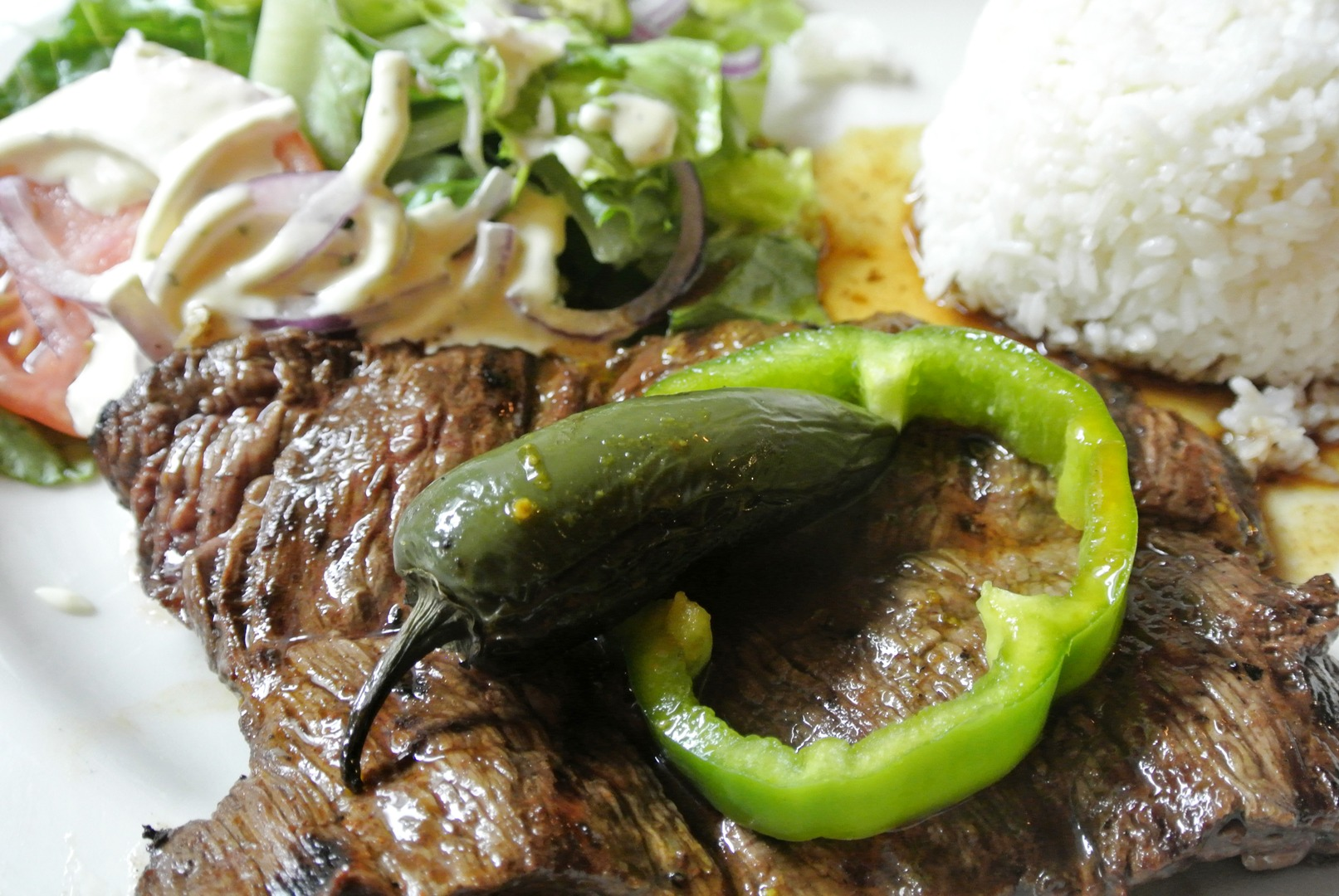 Mesquite grilled skirt steak topped with a jalapeño and green pepper with a salad