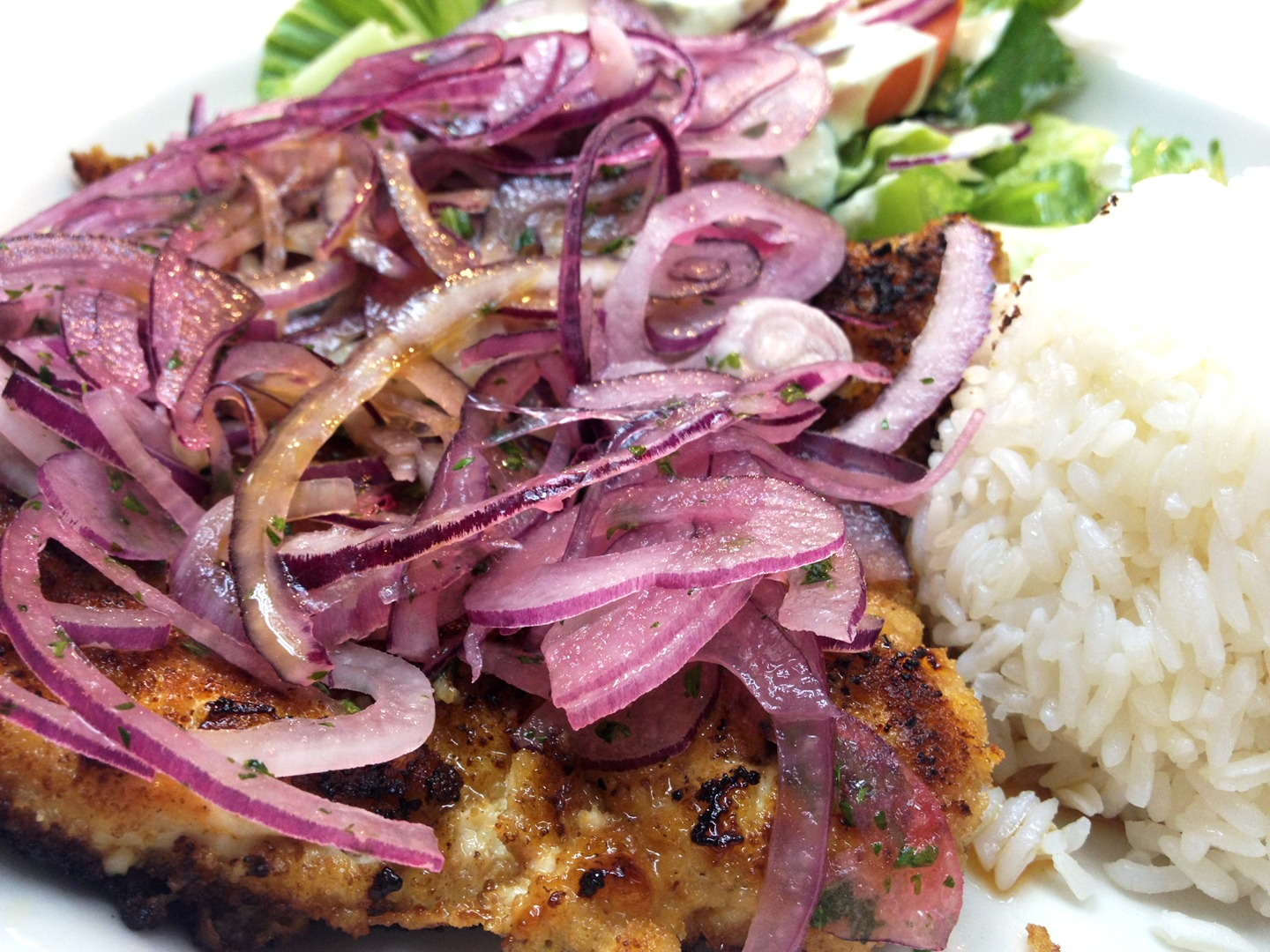 Grilled fish topped with strings of red onions and a side of white rice and salad.