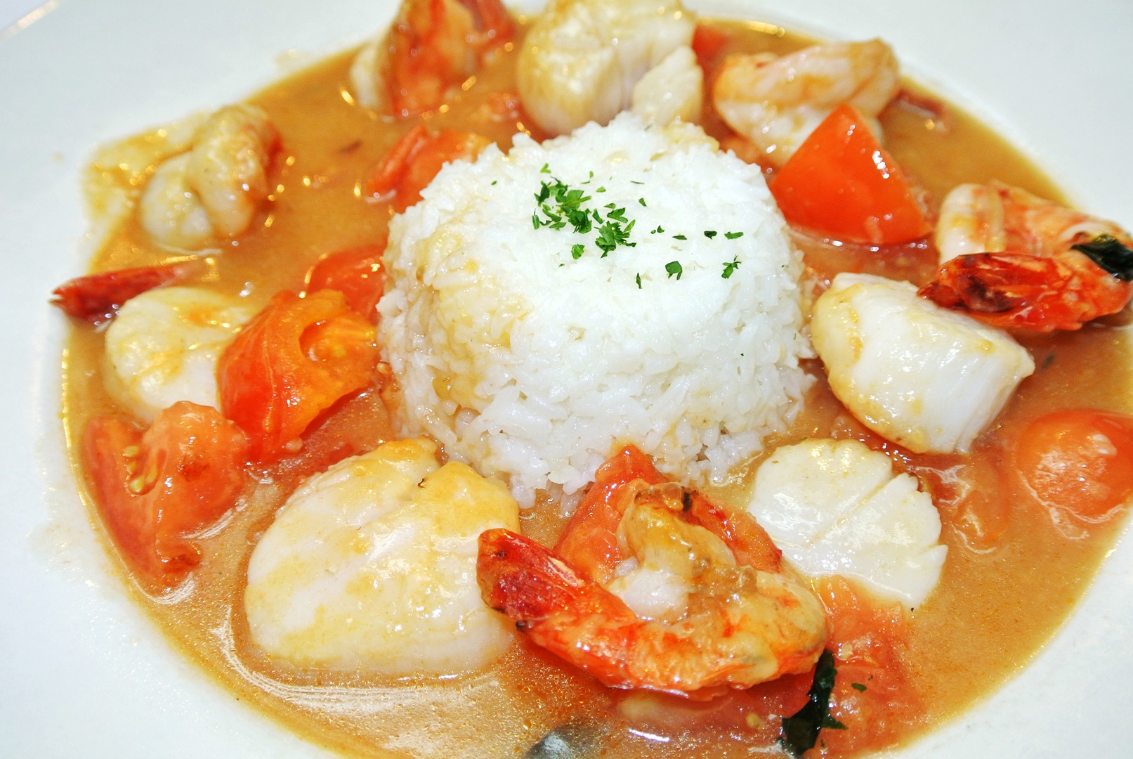 Seafood soup with shrimp, scallops and tomatoes witha  lump of white rice in the center.