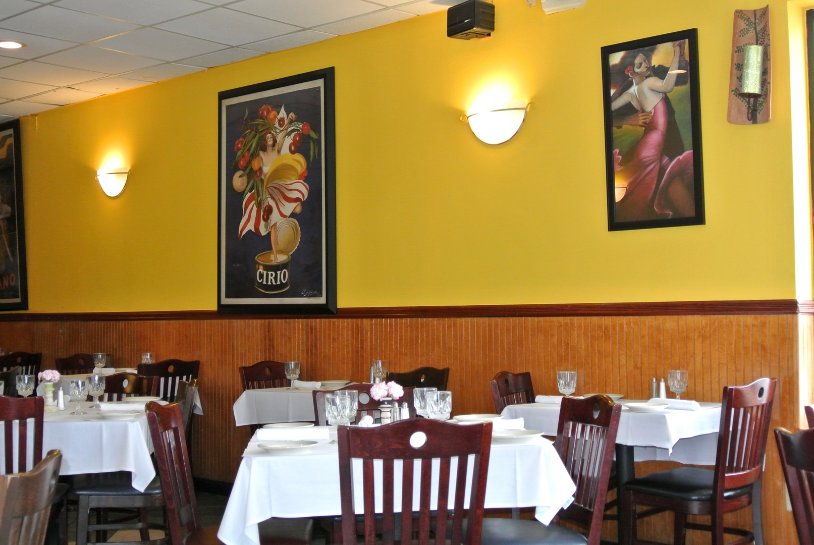 Empty set up tables in a restaurant with yellow walls and festive wall art