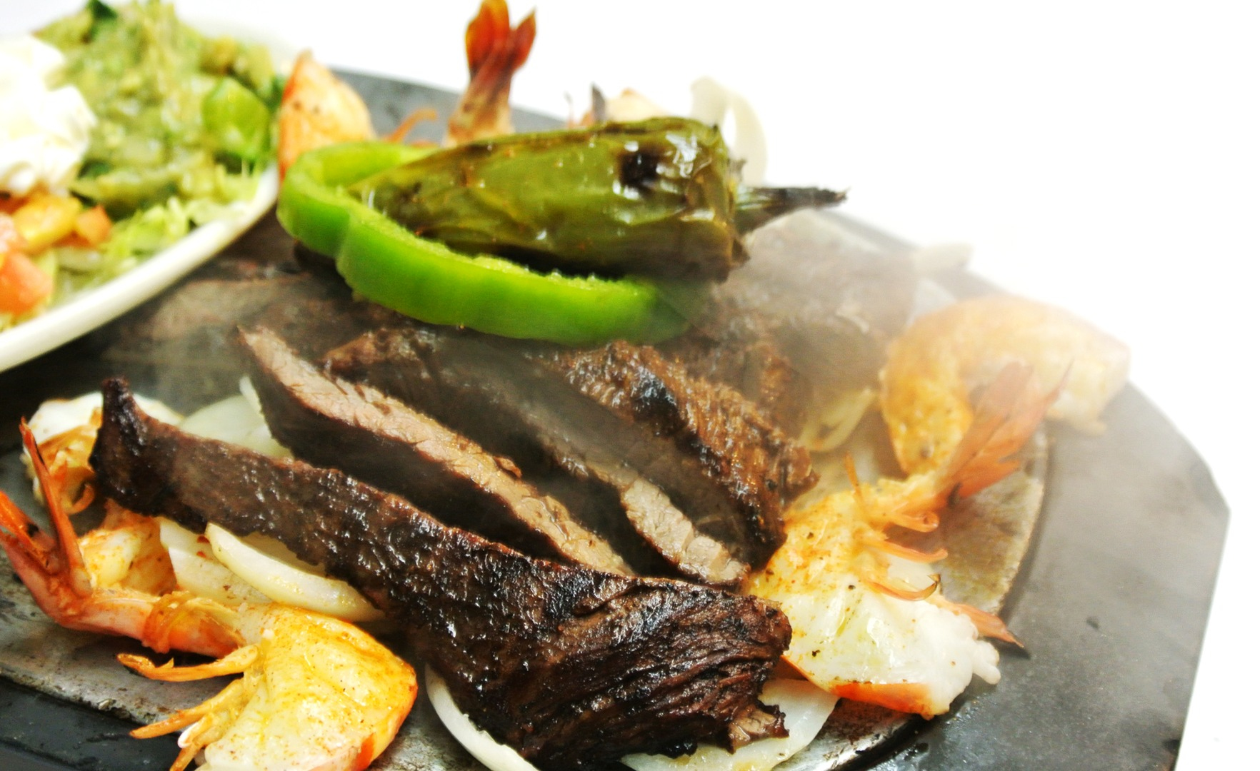 Sliced steak with sliced shrimp topped with green peppers