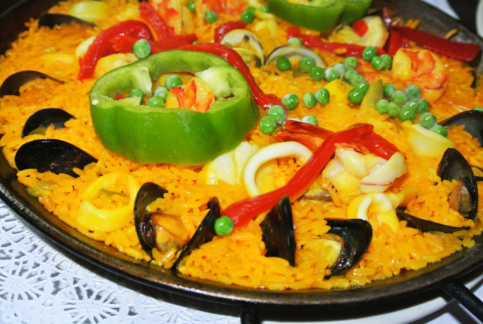Seafood paella with yellow rice, mussels, calamari, peas, and red and green peppers