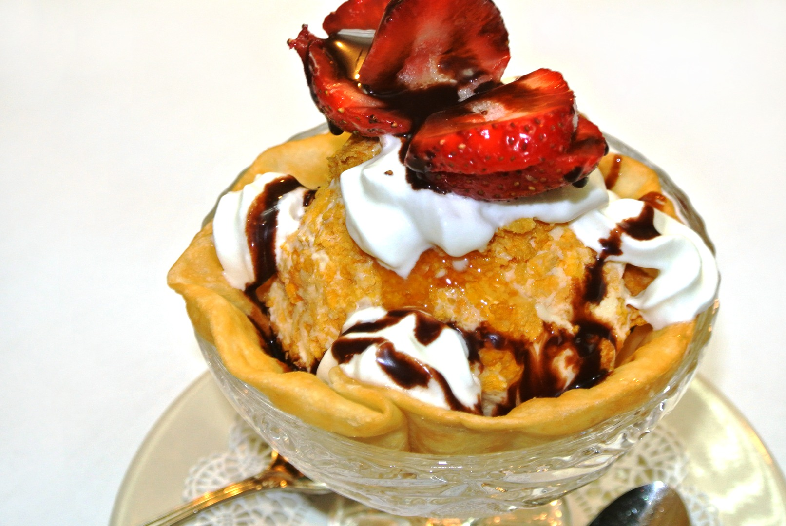 Fried ice cream topped with whipped cream and strawberries with a chocolate drizzle