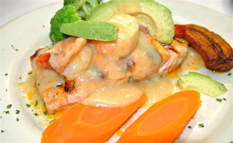 Grilled salmon topped with shrimp, avocado, and a creamy sauce with broccoli and sliced carrots on the side