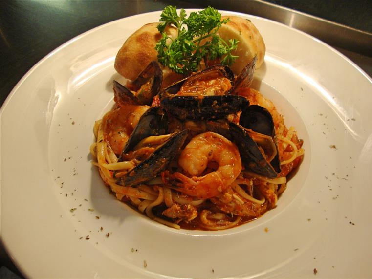 Seafood linguini. Shrimp And Mussels In A Zesty White Wine Lemon Caper Marinara, Topped With Feta Cheese And Olives. Served Over Linguini With Garlic Ciabatta